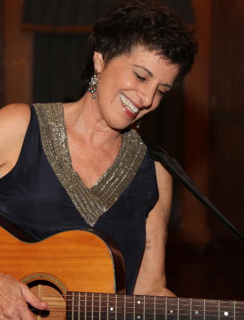 Linda Hirschhorn, smiling, holding a guitar